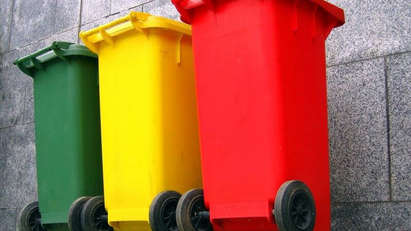 Grüne, gelbe und rote Mülltonne an Wand