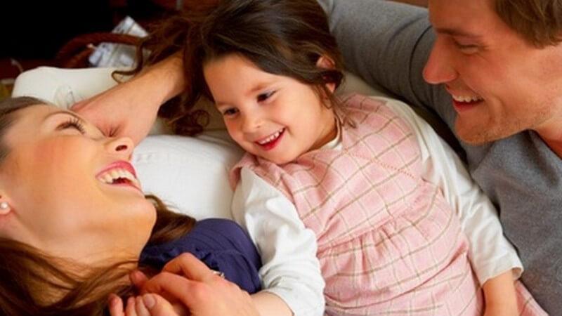 Lachende, fröhliche Familie mit kleiner Tochter auf dem Sofa, sich gegenseitig zugewendet