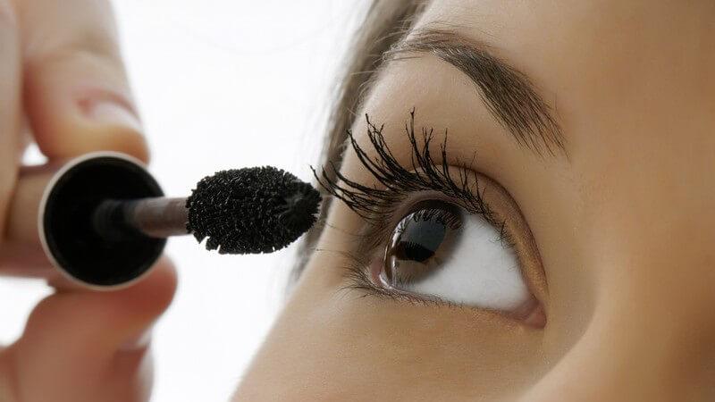 Nahaufnahme Frau mit braunen Augen trägt Mascara auf