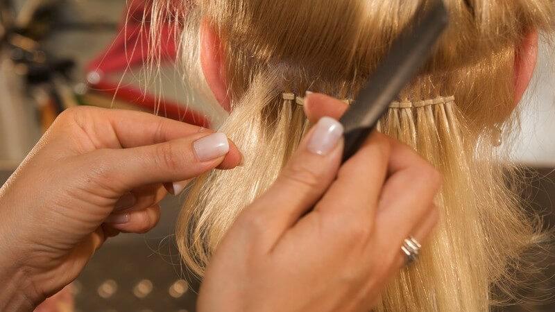 Junge Frau bekommt Haarverlängerung beim Friseur
