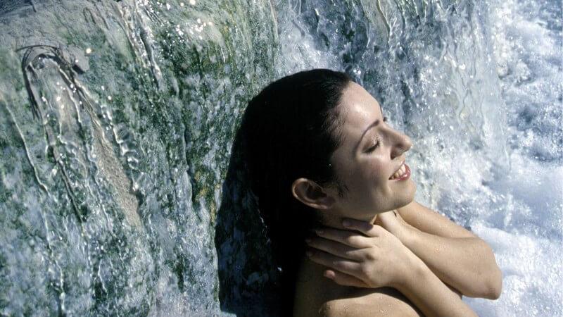 Nackte Frau steht vor Wasserfall