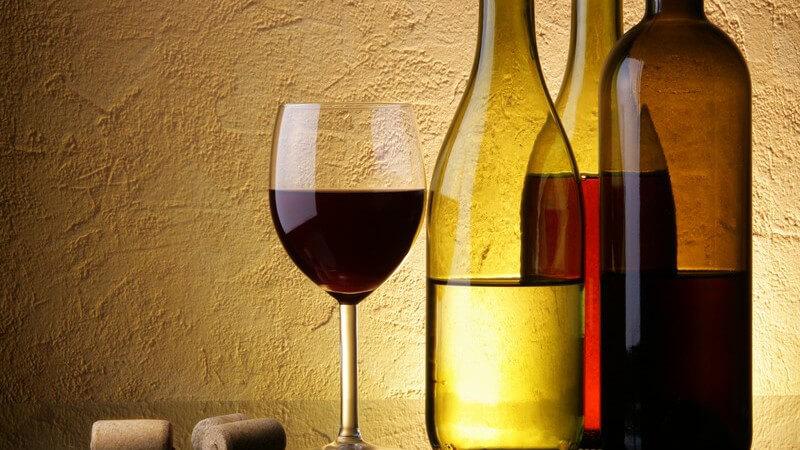 Drei Weinflaschen, daneben Glas mit Rotwein und Korken