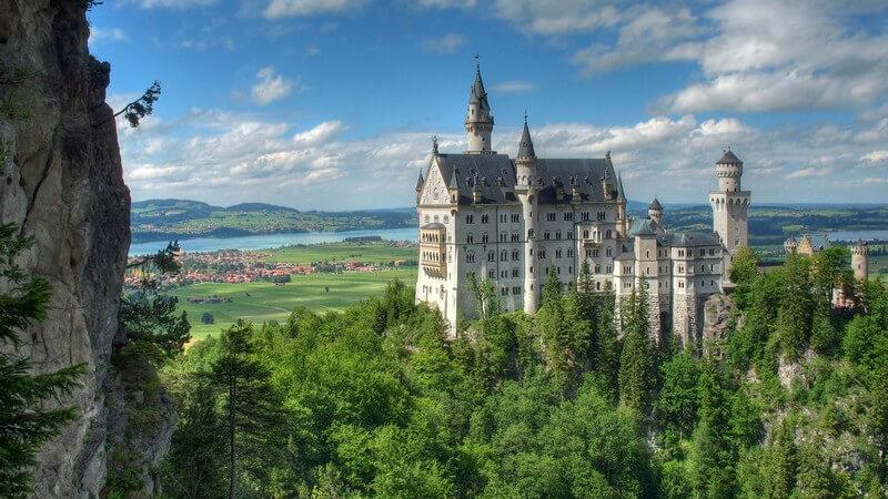 Schloss Neuschwanstein auf waldigem Berg, blauer Himmel und Wolken
