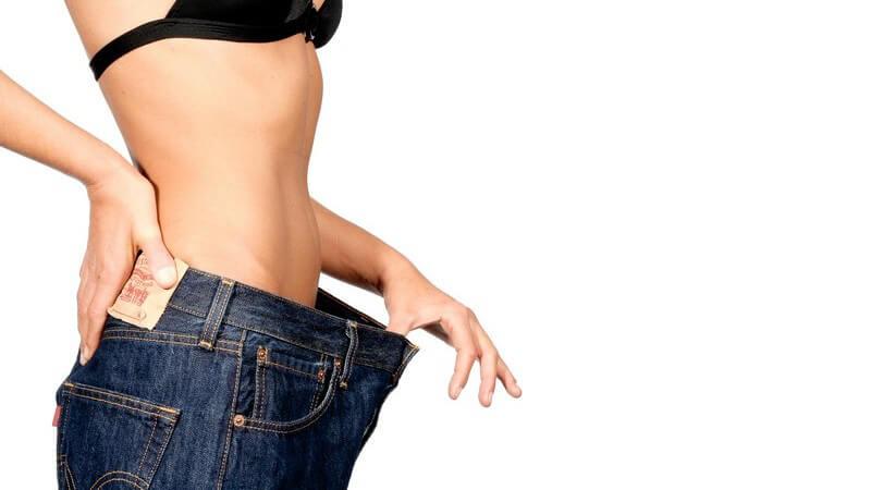 Bauchpartie einer untergewichtigen, dünnen oder sehr schlanken Frau, die eine zu große Jeans trägt, Unterschied