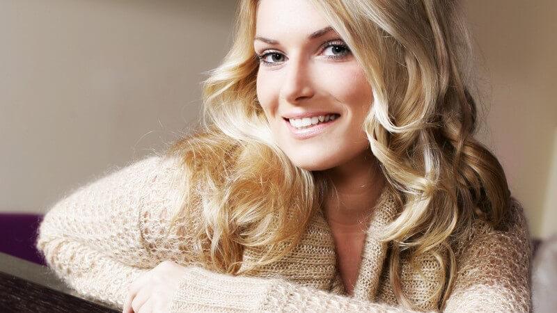 Hübsche, lächelnde Frau mit langen, blonden Locken und beigem Wollpulli