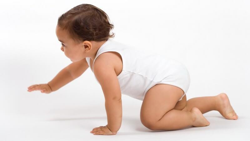 Baby in weißem Unterhemd und kurzen Haaren krabbelt zur linken Seite