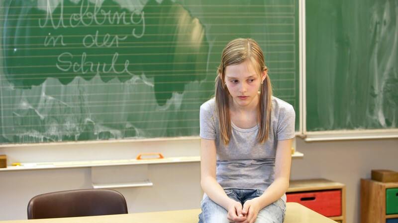 Mobbing in der Schule: Mädchen sitzt traurig und allein auf Tisch in Klassenzimmer