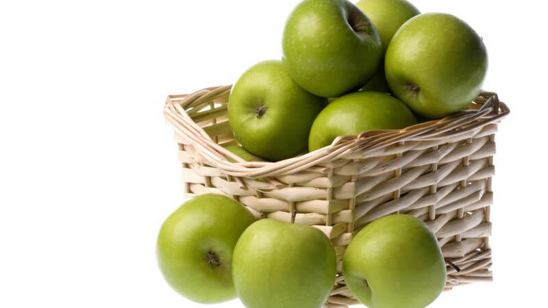 Grüne Äpfel in und vor Korb auf weißem Hintergrund