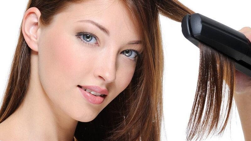Junge Frau glättet sich mit Glätteisen die Haare, weißer Hintergrund