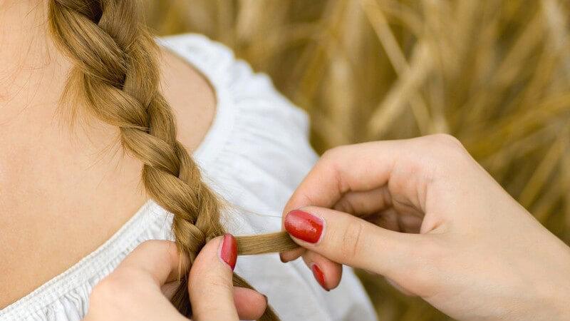 Zopf einer blonden jungen Frau wird geflochten