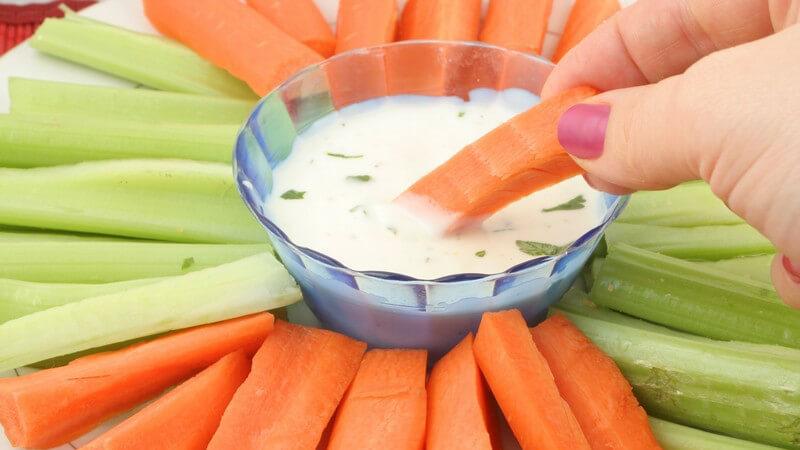 Rechte Hand einer Frau dippt Möhre von einem Gemüseteller mit Möhre und Gurke in Joghurtdip