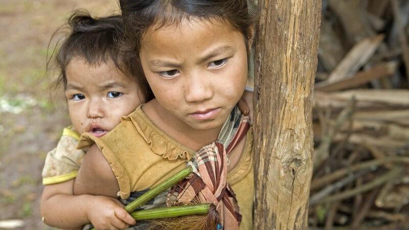 Zwei traurige kleine Hmong Geschwister, leben in Armut