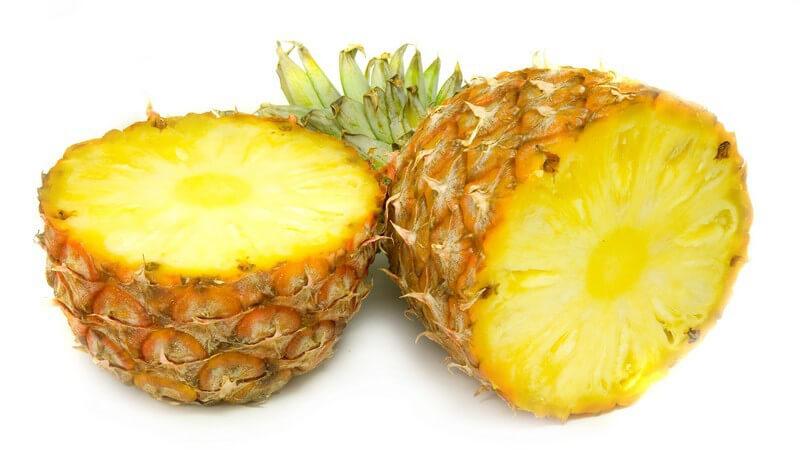 Halbierte Ananas mit grünem Strunk auf weißem Untergrund
