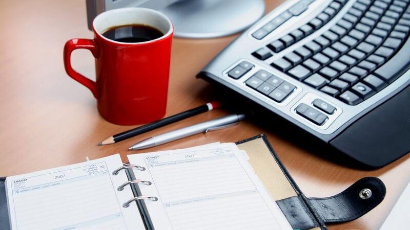 Schreibtisch mit PC, Terminkalender, Stiften und Becher Kaffee