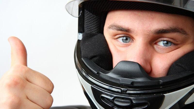 Motorradfahrer mit Helm zeigt Daumen nach oben