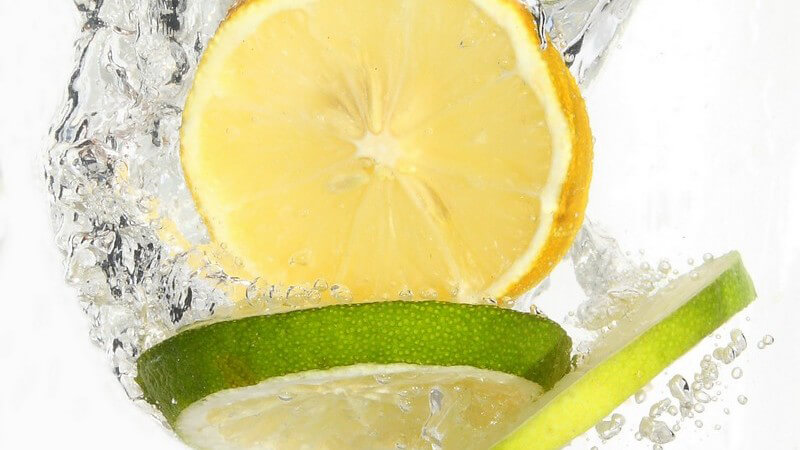 Zitronen- und Limettenscheiben fallen ins Wasser