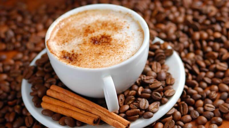 Cappuccinotasse mit Zimtschaum umgeben von Kaffeebohnen und Zimstangen