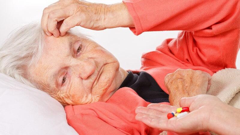 Hand reicht einer liegenden alten Frau in roter Strickjacke mehrere Tabletten