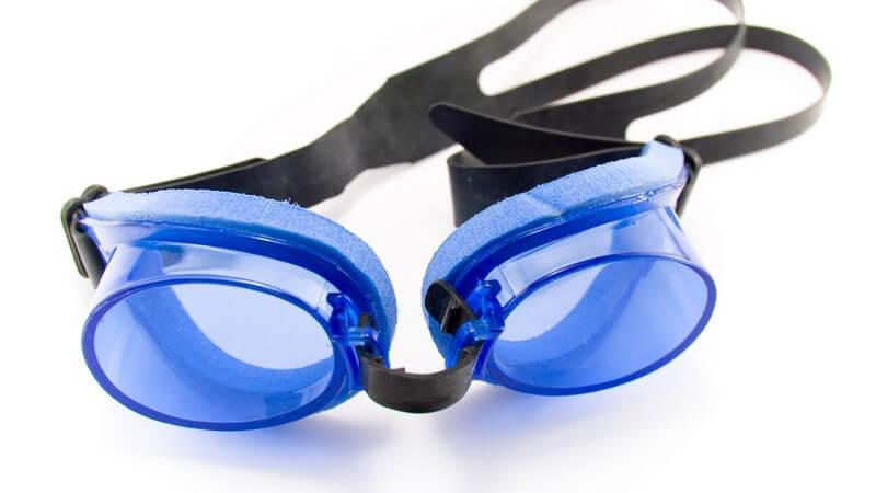 Schwimmbrille mit blauen Gläsern und schwarzem Gummi vor weißem Hintergrund