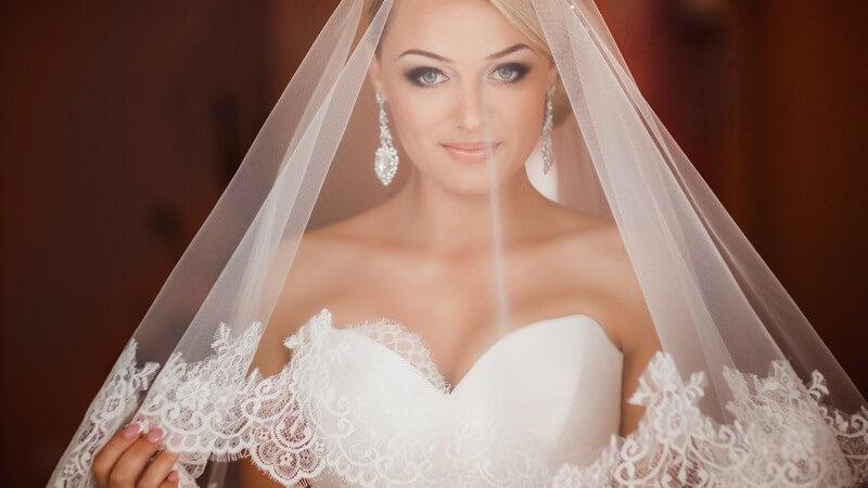 Hübsche blonde Braut mit langen glamourösen Ohrringen unter einem durchsichtigen Schleier