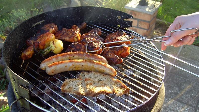 Grillgut auf einem Bratrost auf der Terrasse, eine Hand führt eine Zange zu einem Stück Fleisch