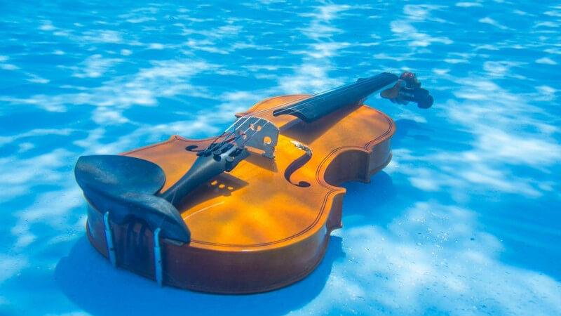 Geige liegt im Wasser am Boden eines Pools