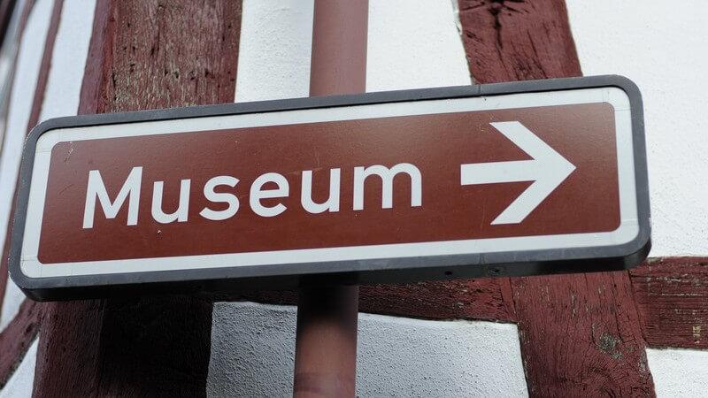 Braunes Schild auf dem in weißer Schrift Museum steht mit Pfeil nach rechts