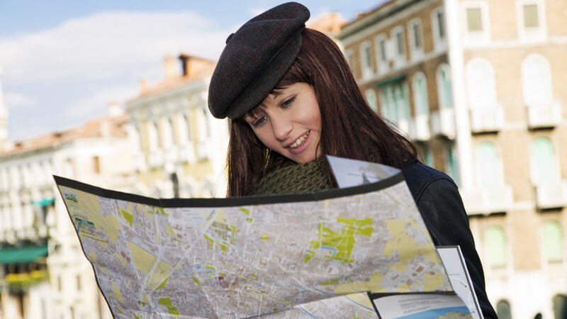 Junge dunkelhaarige Frau mit schwarzer Mütze in Venedig, schaut in einen Stadtplan