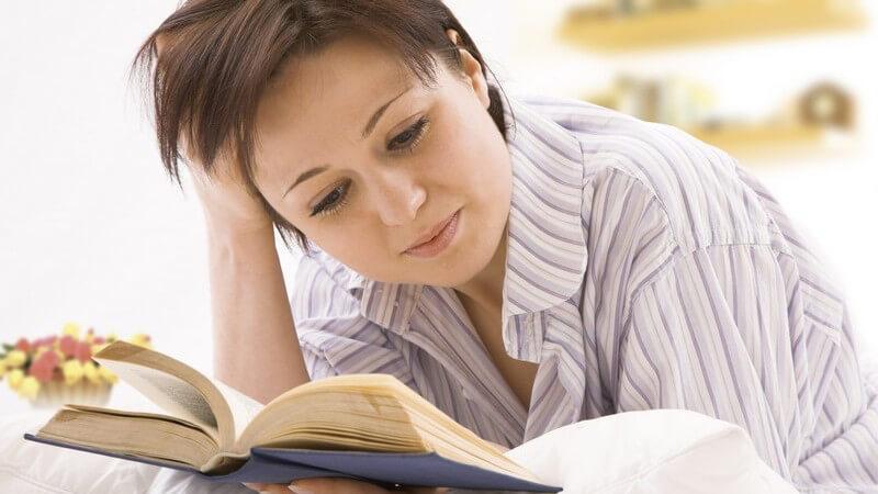 Frau liegt auf dem Bauch und liest ein Buch, die rechte Hand stützt den Kopf