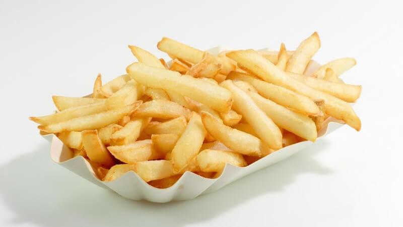 Pommesschale mit Pommes Frites vor weißem Hintergrund