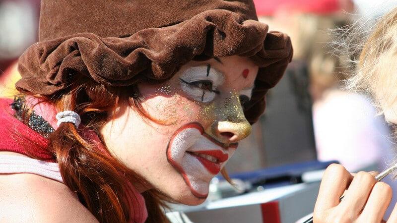 Als Clown geschminkte Frau schminkt Kind, Kinderfest, Straßenfest