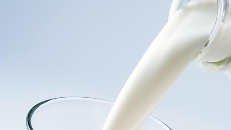 Nahaufnahme Milch aus Glasflasche wird in ein Glas gekippt