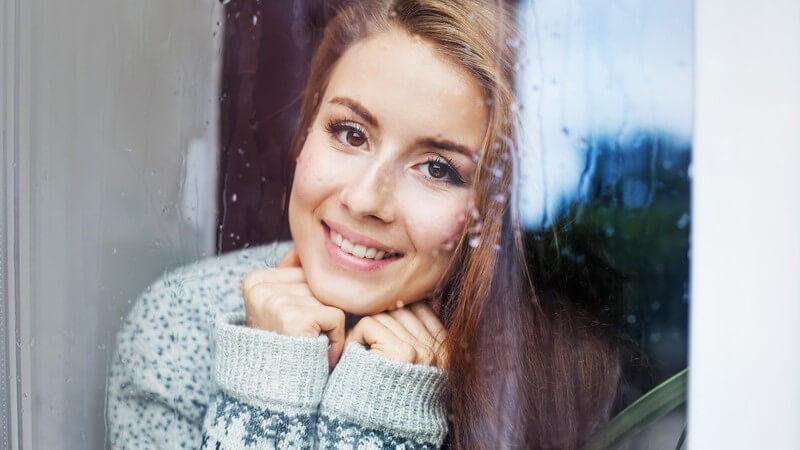 Frau mit langen Haaren und Winterpullover guckt lächelnd und auf ihre Hände gestützt aus einem Fenster
