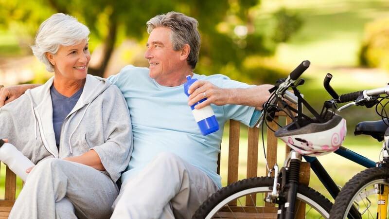 Äteres Paar entspannt auf Parkbank, daneben Fahrräder