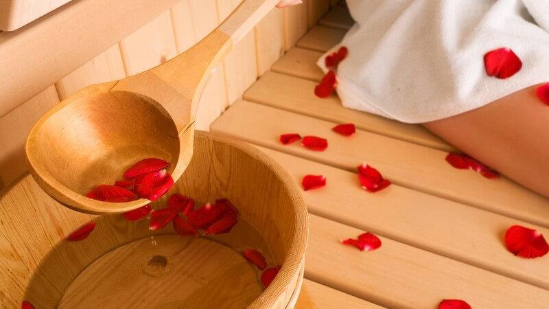 Holzeimer mit Wasser und Rosenblättern in Sauna neben Frau in weißem Handtuch
