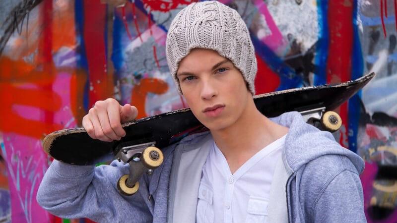 Junge mit grauer Strickmütze trägt Skateboard auf Schulter