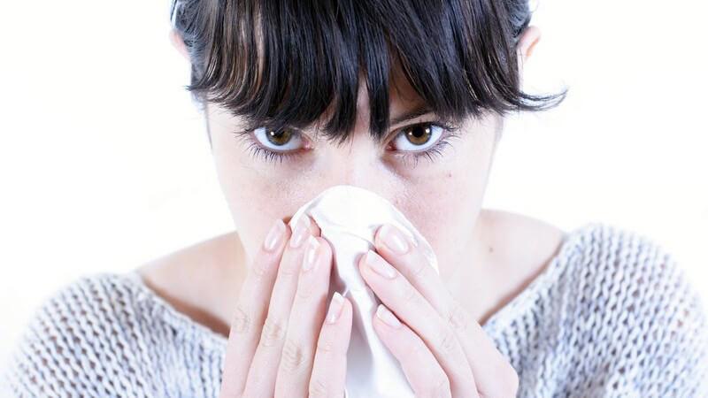 Junge Frau mit schwarzen Haare und im Wollpulli putzt sich die Nase