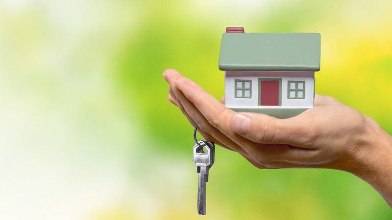 Kleines Modellhaus in einer Handfläsche vor grünem Hintergrund, Schlüssel hängt an einem Finger
