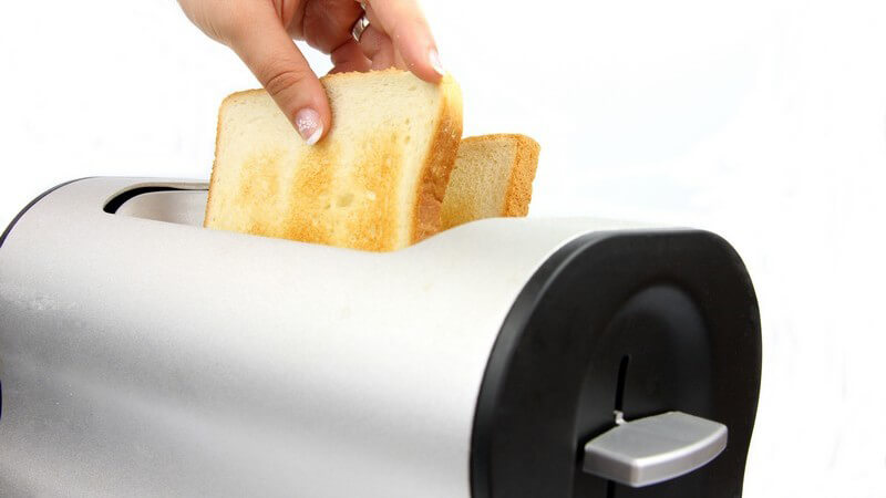 Frauenhand holt zwei fertige Toasts aus dem Toaster