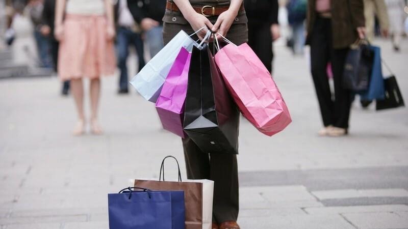 Unterkörper von jungen Frauen mit vielen Einkaufstüten; Kleidung shoppen beim Shoppingtrip