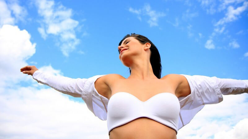 Brünette Frau in Unterwäsche mit ausgestreckten Armen unter blauem Himmel