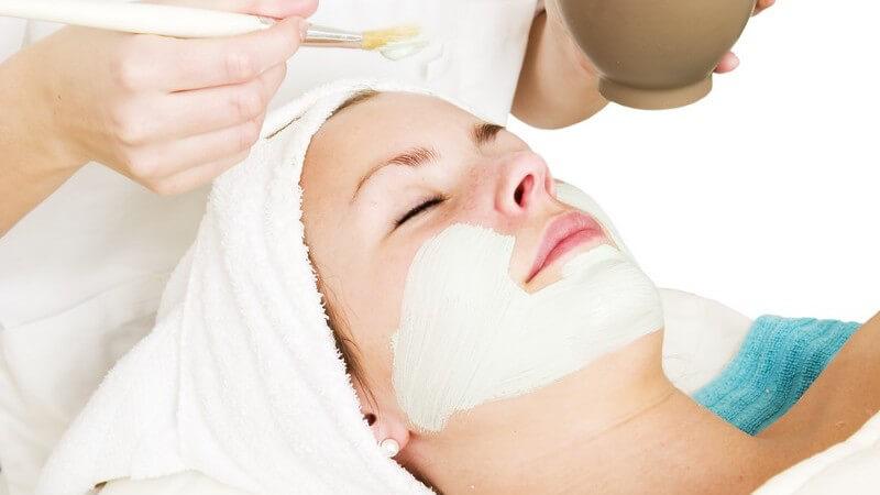 Gesichtspflege - Kosmetikerin trägt helle Gesichtsmaske auf