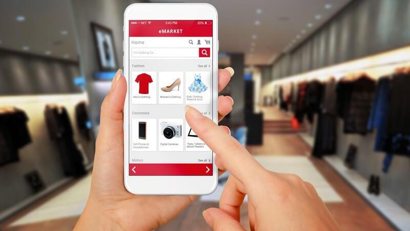 Frauenhände halten ein Smartphone, Shopping von Mode in einem Onlineshop, im Hintergrund ein Modegeschäft