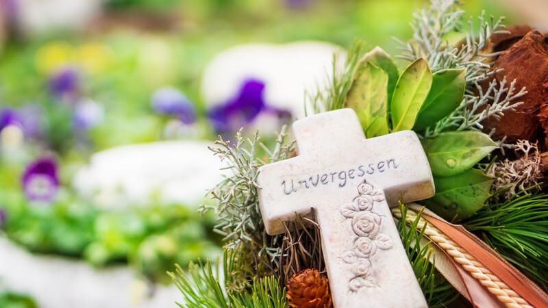 """Nahaufhnahme Grabschmuck auf Friedhof mit Kreuz, auf dem """"Unvergessen"""" geschrieben steht"""