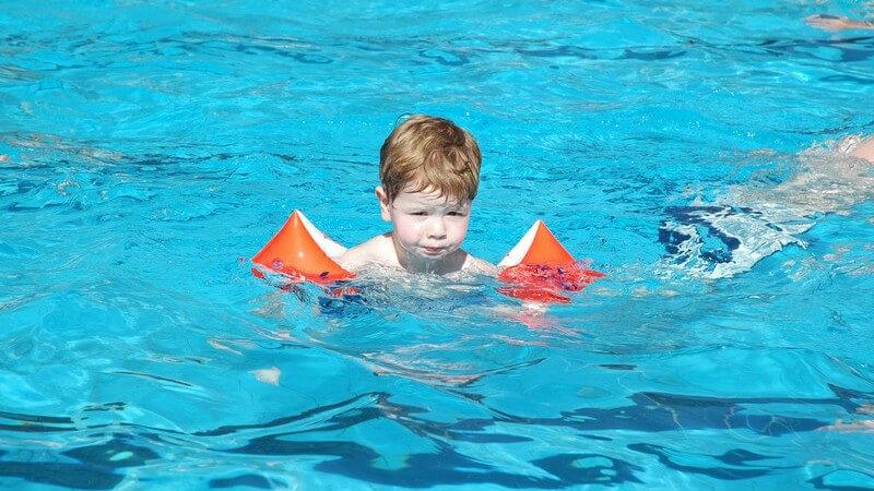 Kleiner mittelblonder Junge (ca. 4 Jahre) ist bei Sonnenschein in Schwimmbecken eines Freibads mit Schwimmflügeln