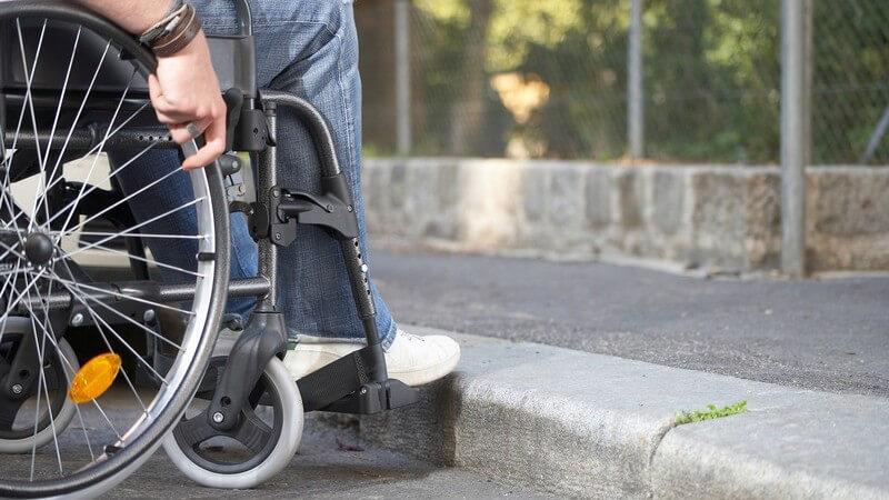Nahaufnahme Rollstuhlfahrer vor Bordsteinkante