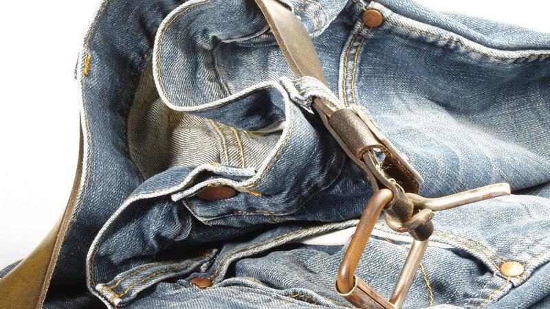 Oberer Teil einer Bluejeans im Used Look mit braunem Ledergürtel auf dem Boden liegend mit weißem Hintergrund