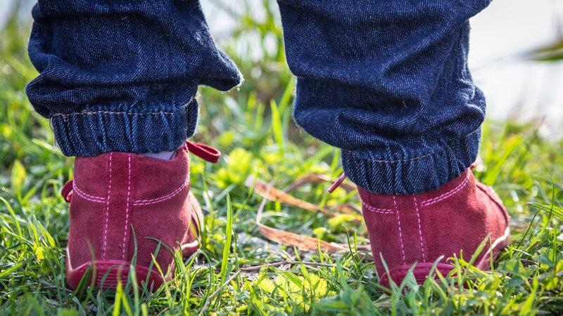 Kleinkind auf Wiese, in roten Schuhen und blauer Jeans