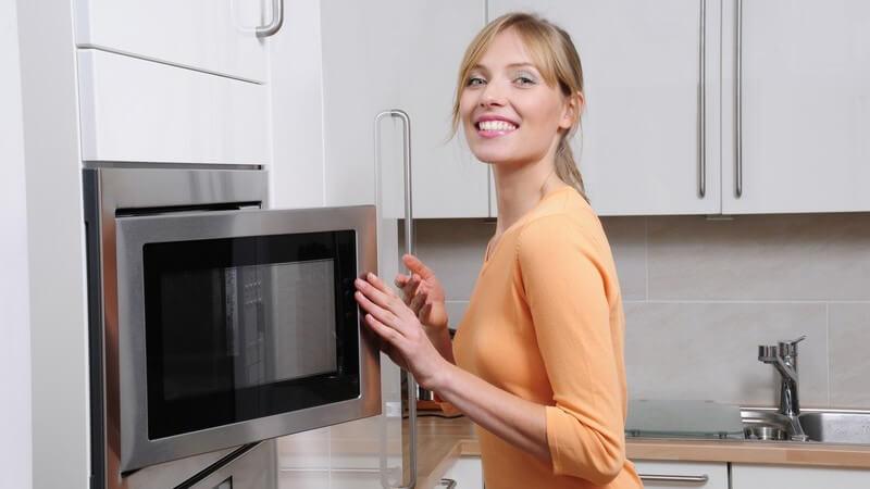 Frau in moderner Küche steht vor Mikrowelle