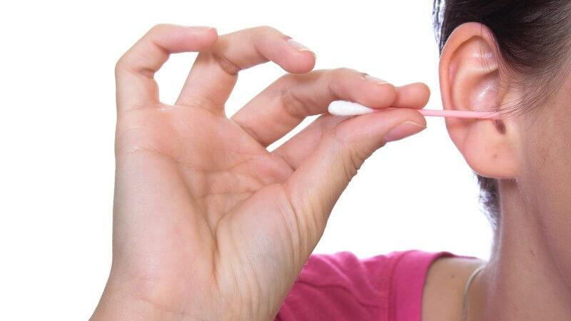 Nahaufnahme Ohr wird mit Wattestäbchen geputzt